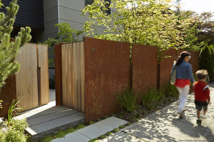 This fence--comprising a rusted steel wall, cedar screen and unique gate--reclaim a garden near a busy intersection in a traditional Seattle neighborhood. Along wtih the screen and gate, slits in the rusted steel wall encourage curiosity about the landscape within. Click through to our blog to see a second image showing more paving stones and garden. Architect: Robert Edson Swain (bobswain.com). Photos Ken Gutmaker (kengutmaker.com).