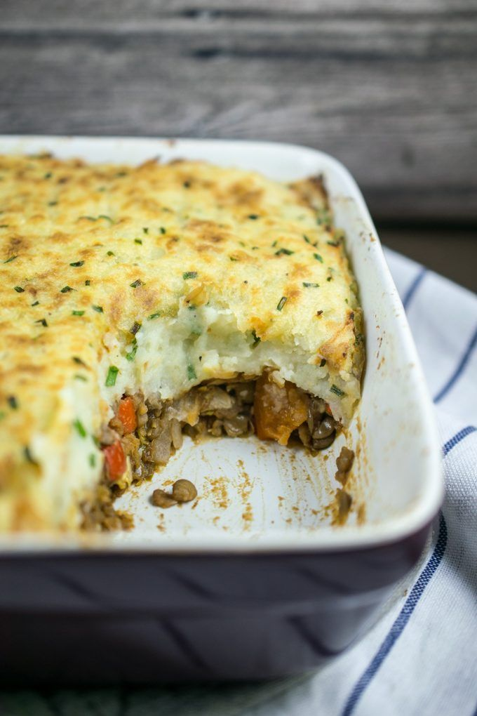 Inside view of vegan shepherd's pie, with a juicy layer of lentils and vegetables, topped with creamy mashed potatoes flecked with chives.