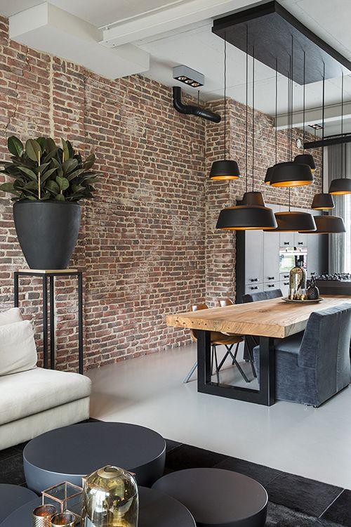"""Liefhebbers van industriële interieurs kunnen hun hartje ophalen bij het zien van deze moderne zwarte keuken. Door de hanglampen op verschillende hoogtes te hangen creëer je een speels effect. De massiefhouten keukentafel met stalen onderstel en de steenstrips met baksteen look zorgen voor een stoere uitstraling. Foto: Denise Keus – """"Stijlvol Wonen"""" - © Sanoma Regional Belgium N.V."""