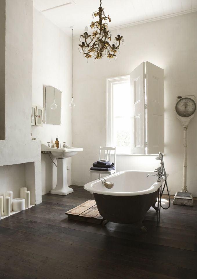 chandelier in the bathroom! And the thick white candles. The bathtub in the middle of the room doesn't look practical but it's gorgeous! (Originally from Gardener & Marks)