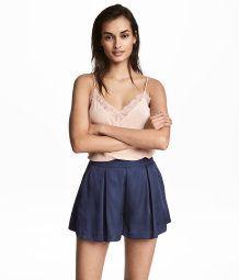 Ett par korta shorts i satin med lagda veck upptill. Shortsen har sidfickor och vida ben. Dold dragkedja i sidan.