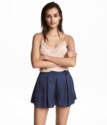 Short satin shorts with pleats at top, side pockets, and wide legs. Concealed zip at side.