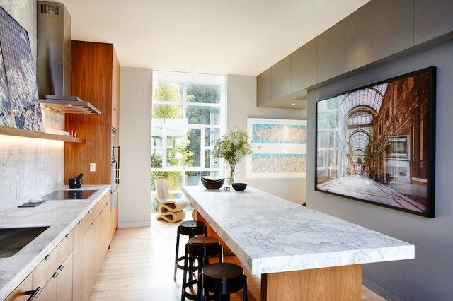 Here, a two-inch slab of Calacatta marble tops the walnut island and pulls in the grey tone of the facing accent wall.