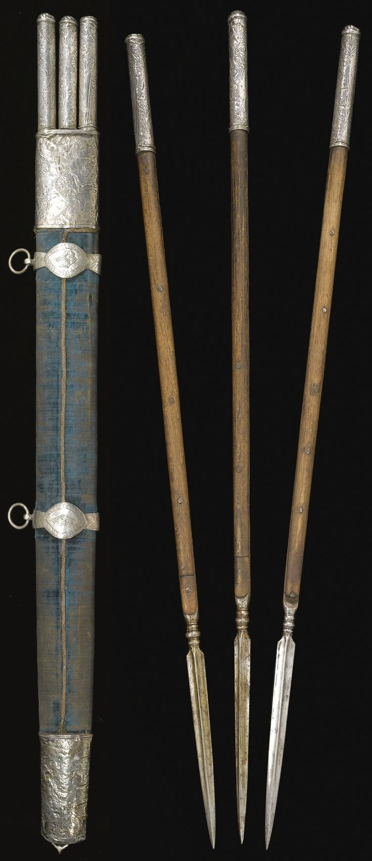 Ottoman throwing spears (Jarids) and quiver, circa 1680, the plain steel arrowheads with quadrangular tips, wooden hafts and silver terminals formed as tubular sockets decorated with chased and engraved medallions containing floral sprays, the wooden quiver mounted with blue-green velvet, the silver chape, lock and suspension loops decorated en suite, the lock with traces of gilding, 83.8cm.