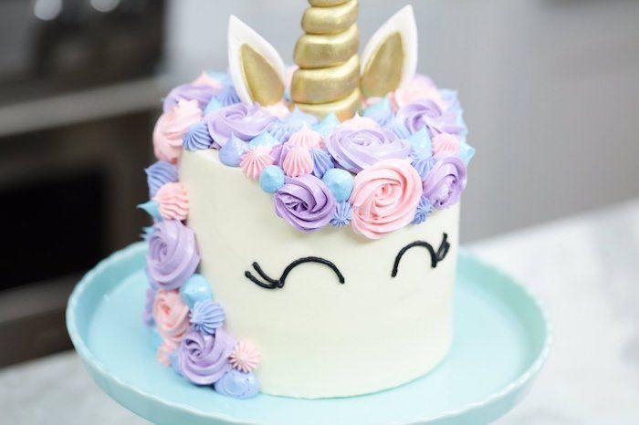 einhorn kuchen dekif und einhorn torte mit einer langen mähne aus sahne, ein langes goldenes horn und schwarze augen und lula, pinke und blaue rosen
