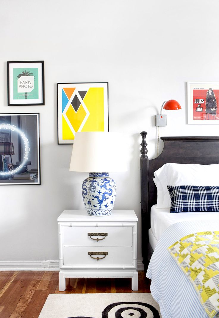 White bedroom with colorful artwork, blue and white porcelain table lamp