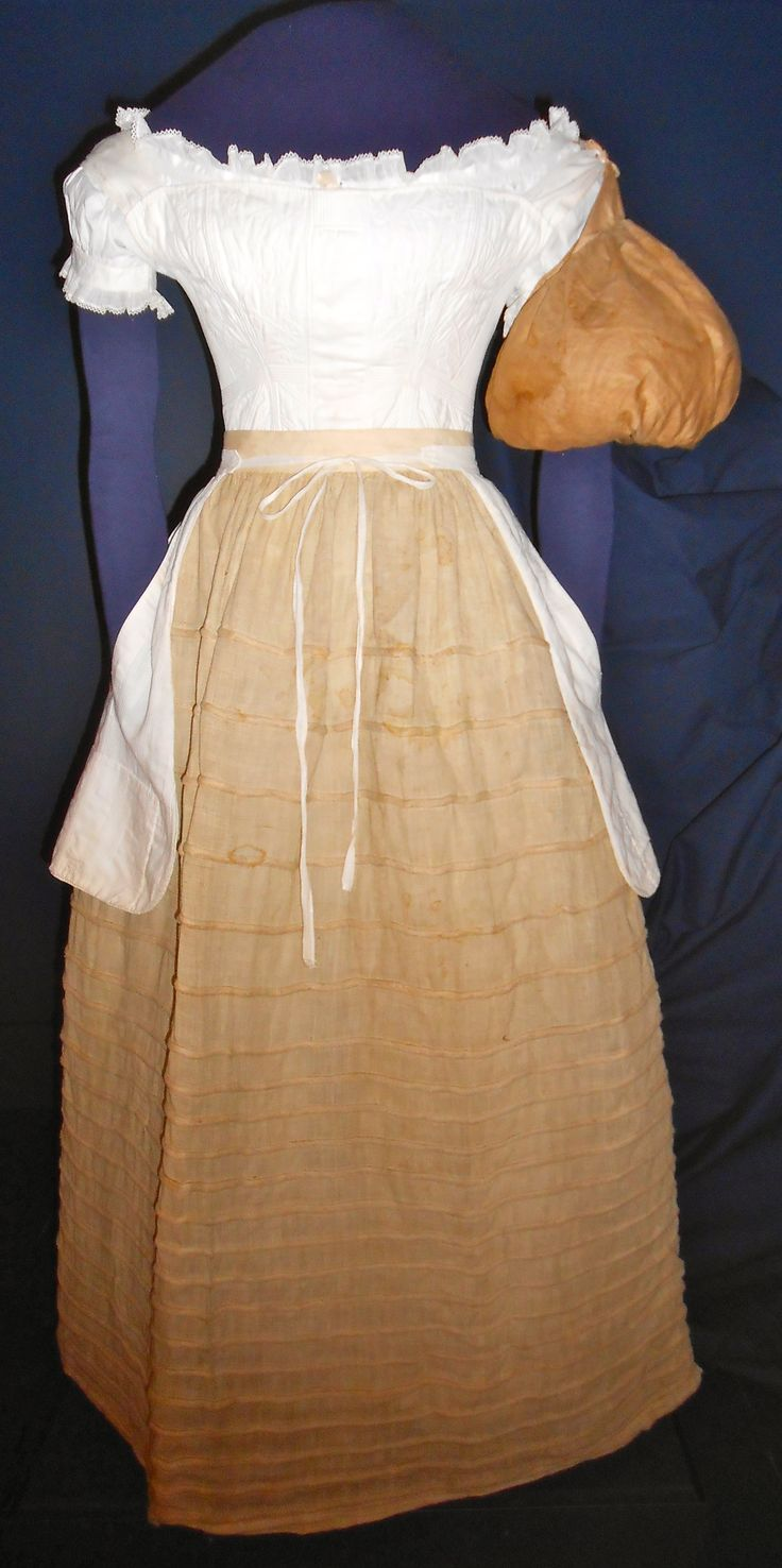 This is what a lady wore underneath her 1825-1830 gown; corset, chemise, and corded petticoat.  The pockets worn over the petticoat tied around the waist.  Sleeve puffs gave a fullness to the large sleeves popular in the late 1820s-1830s. See 1825-1830 red lapis printed calico dress on this page.  Susan Greene Collection at the Genesee Country Village & Museum, Mumford, NY.