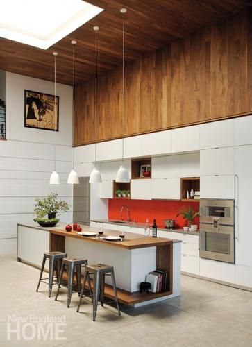 A wall of walnut brings warmth to a large loft-like kitchen. Photography by Eric Roth