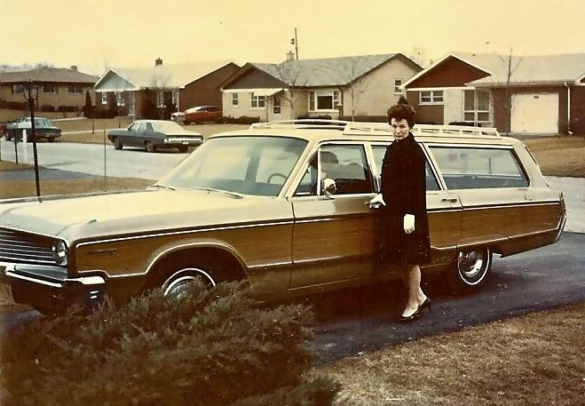 Mom posing next to her 1968 Chrysler Town and Country Station Wagon with AirTemp Air-Conditioning in front of our split level in La Grange, Illinois.