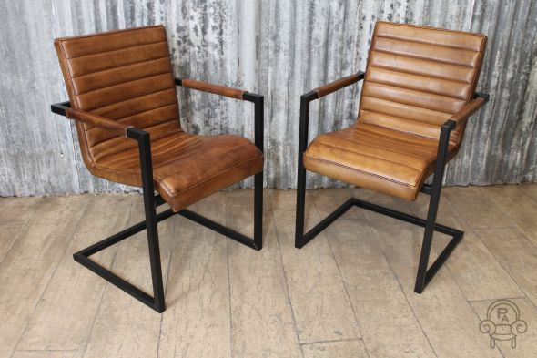 Vintage style leather armchair.This superb quality tan leather dining or occasional chair has beautiful stitching detail. Supported by a black steel...