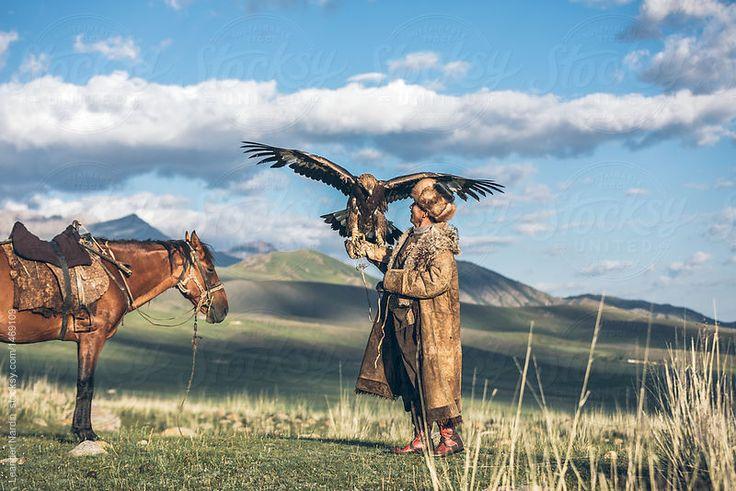 Golden eagle landing on the arm of kyrgyz eagle hunter by Leander Nardin for Stocksy United