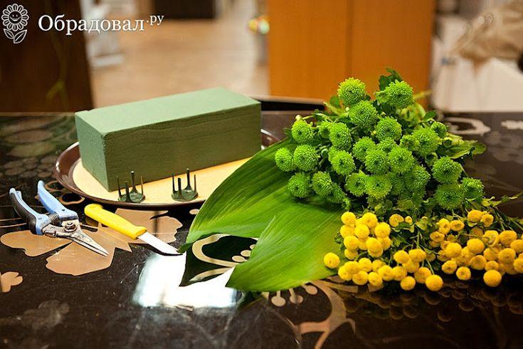 Нам понадобится:   кустовая хризантема двух цветов (по 4-5 веток каждого цвета);  крупные листья – например, монстеры (или зеленая ткань, или зеленая бумага);  флористический фиксатор (или карандаши, соломинки, палочки);  пиафлор (3 кирпича);  блюдо (или тарелка, или другой поддон);  две пуговицы (или бусины);  цветная бумага или толстая цветная шерстяная нить;  флористический нож, а также секатор.