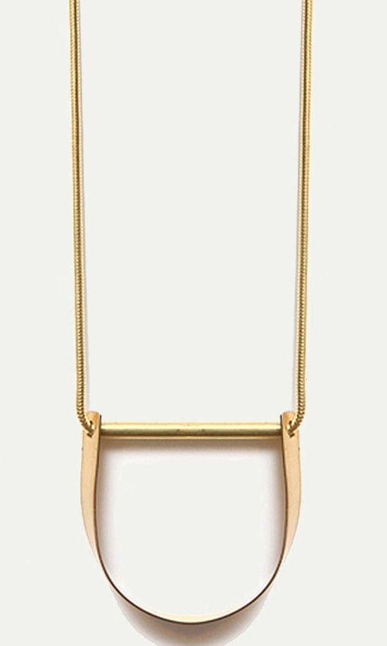 Simple shapes can make a strong statement. Case in point: this brass curved bar pendant hanging on a snake chain.