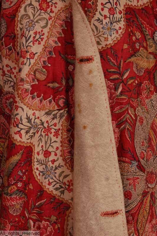 Kamerjas in katoen sits indisch rood, bedrukt band wit/veelkleurig + bloempot veelkleurig; voering: wol naturel model tot net over knie, schuin over elkaar vallend, lange aangeknipte mouw, boord iets V-vormig Jas uit één stofbreedte, mouw ter hoogte van elleboog verlengd met aangenaaid deel. Steekzak (linnen) en split in zijnaden afgewerkt met 2 cm brede zakklep. Rug midden onder vertikaal naadje. Mouw gerimpeld aan manchet 4cm. Sluiting: boord met haak en trens, verder 2 stofknopen. Boord…