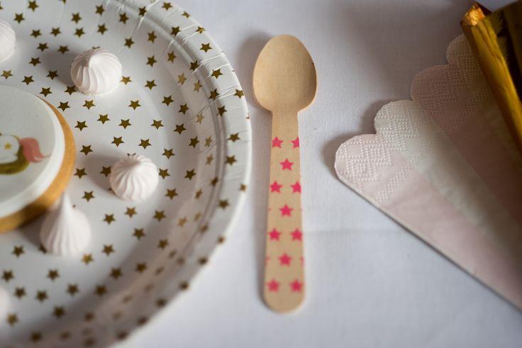 Papierowe talerzyki w złote błyszczące gwiazdki. Drewniane łyżeczki w różowe gwiazdki.