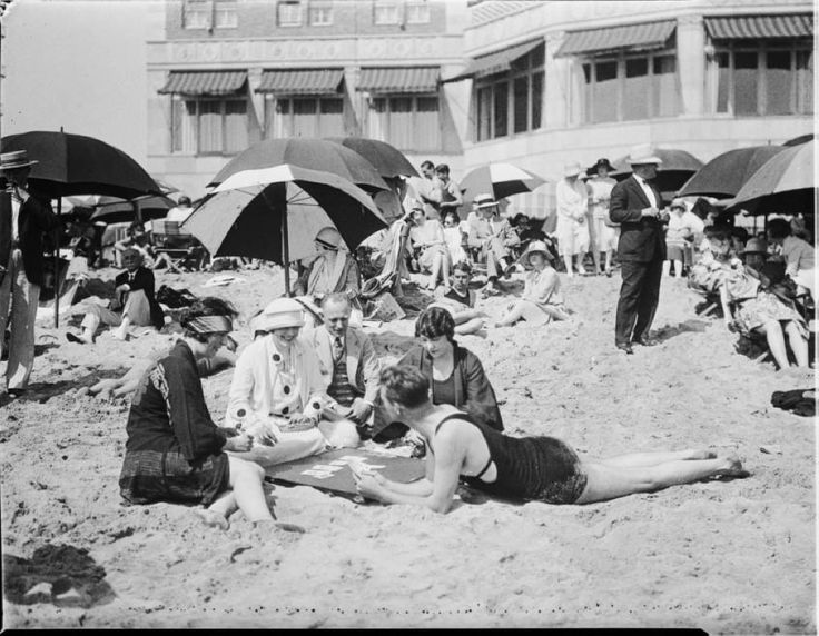 California Historical Society Collection, 1860-1960 :: Photograph of a beach scene, showing people relaxing next to umbrellas, [s.d.]. In the foreground, a group of people can be seen sitting on a sandy ground, wearing old-fashioned swimming suits, while playing a game of cards. Behind them, additional people are visible while sitting under beach umbrellas. Sand covers the entire ground area. A partially visible building serves as the backdrop.
