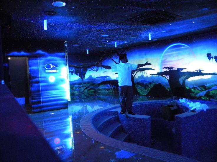 Altra foto della piscina con rappresentazione di paesaggi fantasy. il pavimento è realizzato in resina eposidica con all' interno conchiglie e stelle marine reali e trattate con colori fluo
