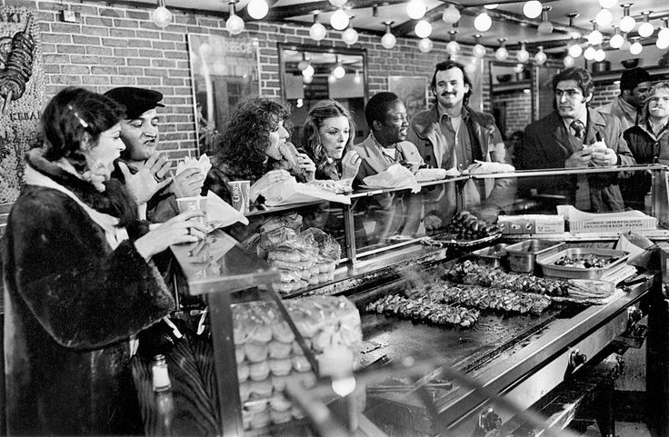 "Gilda Radner, John Belushi, Laraine Newman, Jane Curtin, Garrett Morris and Bill Murray getting Greek food after wrapping an episode of ""Saturday Night Live"" (1977)."