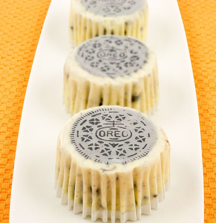 A photo of 3 Oreo cookies and cream cheesecakes with Oreo cookie side facing up on a white plate, placed on an orange placemat.