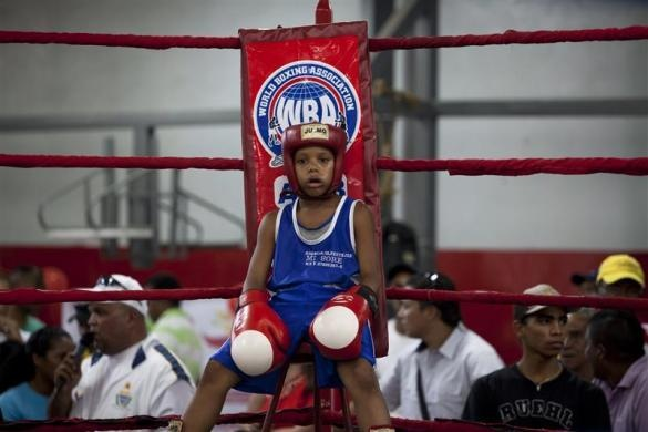 Alex Mayora, 12, rests during a fight in an Olympics-style street boxing championships in the low-income neighborhood Petare in Caracas February 9, 2011.  REUTERS/Carlos Garcia Rawlins
