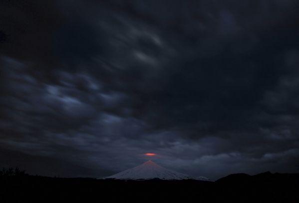 Вид навулкан Вилльярика изгорода Пукон, Чили. Извергающийся смарта 2015-го вулкан Вилльярика расположен вПатагонских Андах иизвестен озером лавы, образовавшимся вего кратере после извержения 1985года.