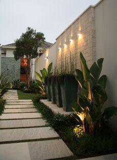 Caminho da lateral com vasos em tom jade, iluminação Luminni e pedras Palimanan.