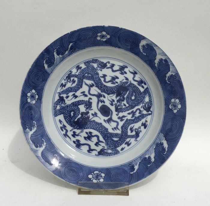 """Een blauw en wit bord met draken die de parel - China - C. 1700 jagen  Een zeldzame Chinese blauwe en witte porseleinen plaat beeltenis van twee draken die de parel achter.De grens met een gedeeltelijk golf ontwerp en bloemen.De achterkant is versierd met gunstige boeddhistische symbolen en binnen de voet-velg een Kangxi """"shop"""" mark in dubbele blauwe cirkel.Het ontwerp is in Chinese smaak.Dimensie; diameter 21 cm.Voorwaarde: een gestabiliseerde haarlijn 5 cm lang nauwelijks zichtbaar aan de…"""