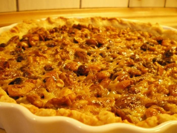 Nøddetærte med flødekaramel. Mørdej, hasselnødder, valnødder, pecannødder og mandler bundet sammen af smuk, cremet flødekaramel. Servér fx med vaniljeis.