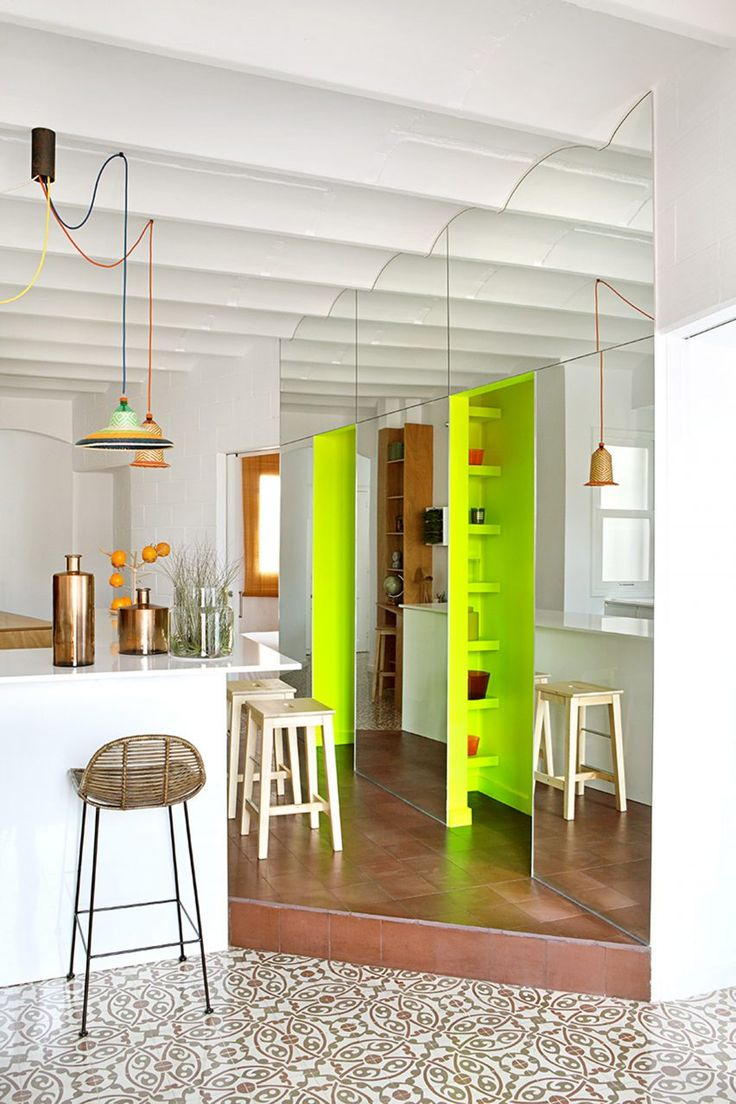 The 65-square-metre Piso Pereiv44 flat is divided into halves by a continuous wall, which is punctuated by fluorescent green storage spaces that are covered in a mirrored panel.