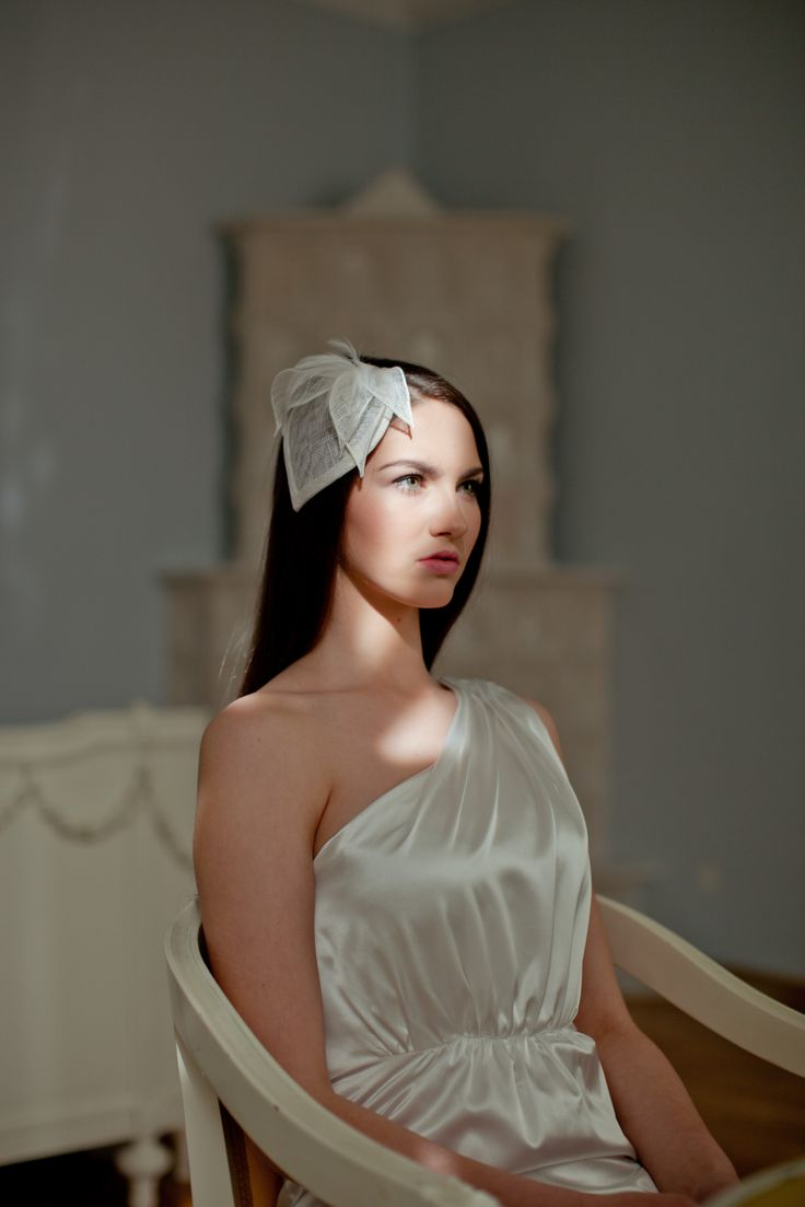 The bridal hat is completely hand made: layers of sinamay blocked on hat block, wired and trimmed it with feathers and sinamay petals made of the same material.   The hat attaches to hair with hair comb. It can be easily placed to any hairstyle. Matching birdcage is also available.