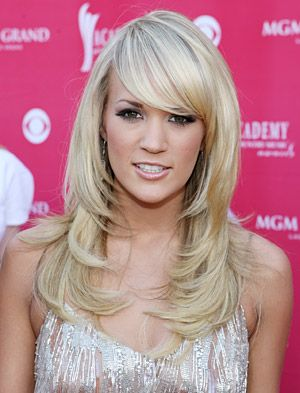 Deep side-swept bangs and tons of oomphy volume kick off Carrie Underwood's flaxen face-framing layers.
