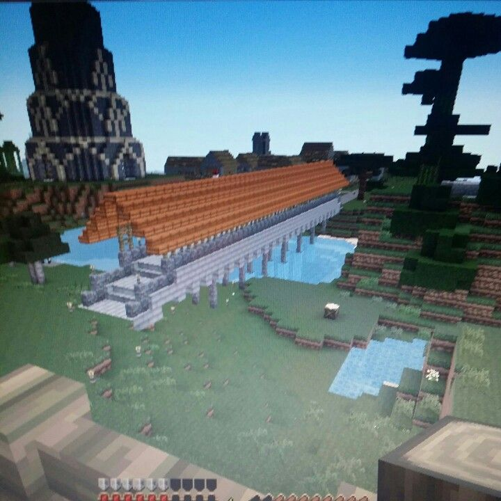 foreground covered bridge background tower and npc village tower and bridge built by minecraft