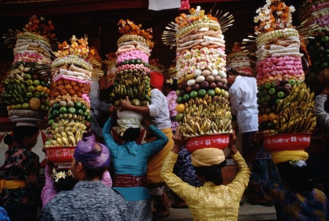 Women in a Balinese village carry banten offerings to the gods which can weigh up to fifty pounds. After the ceremony, the banten are brought home to be consumed by the families.