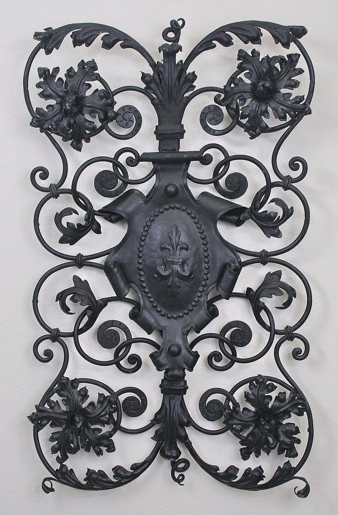 Wrought iron grille, Cyril Colnik, Milwaukee, late nineteenth or early twentieth century    Wrought iron grille with repoussé fleur-de-lis at center, designed by Cyril Colnik, Milwaukee.    This object is the property of the Villa Terrace Decorative Arts Museum. This image is part of the Wisconsin Decorative Arts Database, a digital archive of Wisconsin objects. For more information, see content.wisconsinhistory.org/u?/wda,1594
