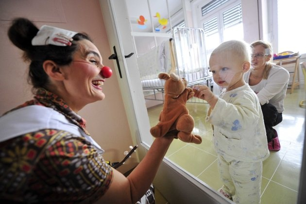 Member of Red Noses clown doctors plays with children in a clinic for infectious diseases in Ljubljana