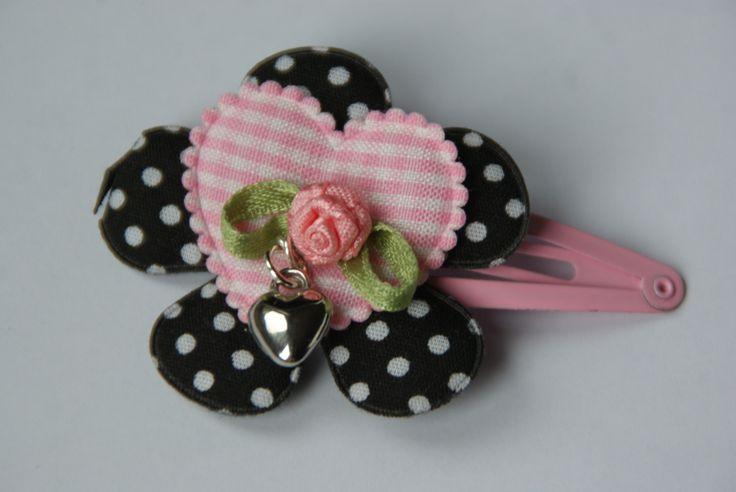 Mooie haarknip met zwarte bloem met stippen en daar bovenop een geruit roze hart. Met een kleine bloem met bedel van een hart eraan.Door een nieuw systeem is het knipje zo te draaien dat het steeds mooi in de haren zit aan welke kant je de knip ook draagt.  www.lotenlynn.nl https://www.facebook.com/lotenlynnlifestyle