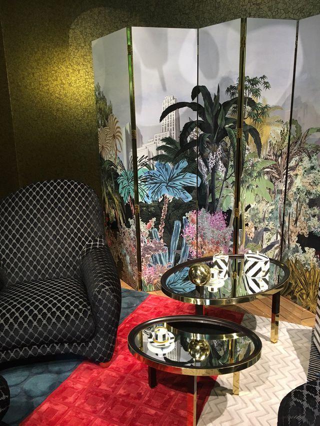 Un coin salon avec des styles mélangés, un paravent à motifs tropicaux et un tapis rouge en velours