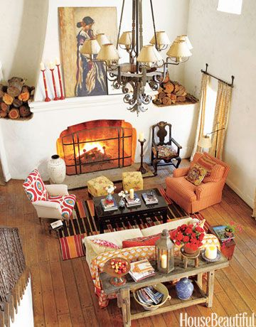 Designer Kathryn M. Ireland's California living room showcases an autumn color palette—ranging from pale yellow, soft pumpkin orange, and deep crimson—much like the changing color of leaves. The orange armchair, a custom design covered in George Red from Ireland's fabric collection, faces a Robert Kime chair with reproduction suzani fabric. The rug is from Amadi Carpets. An old farm table holds flea market finds. The chandelier was made in the property's forge in the 1920s.