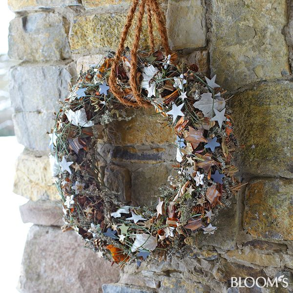 Der Kranz aus Sternen, Blättern, Lärchenzapfen, Kiefernnadeln, Flechtenzweigen, Birkenrinde und Ästen ist überall im winterlichen Garten ein toller Hingucker