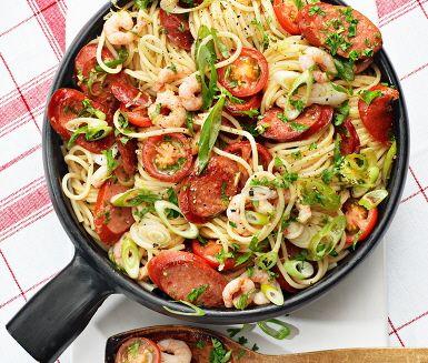 Amirs spanska pasta är en lätt- och snabblagad pastarätt med smakfulla ingredienser som skivad chorizo, salladslök, tomat och räkor. Som tillbehör serveras nykokt spaghetti och ljuvlig ört- och citronolja med persilja och sardeller. Muy Bueno!