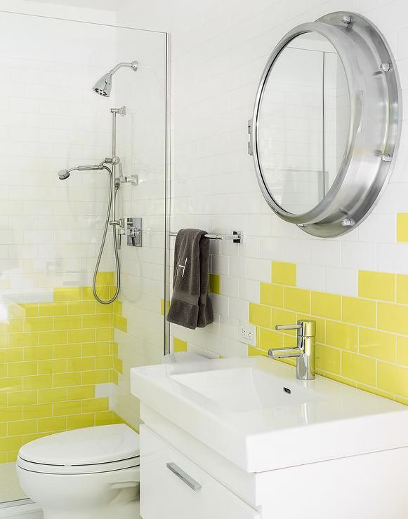 Shared boys' bathroom is filled with a white floating washstand under a Royal Naval Porthole Mirrored Medicine Cabinet lining a wall lined with a mix of white and yellow subway tiles.