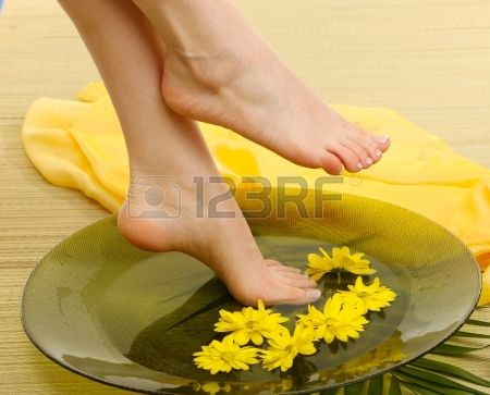 Female feet in spa bowl with water, on bamboo mat