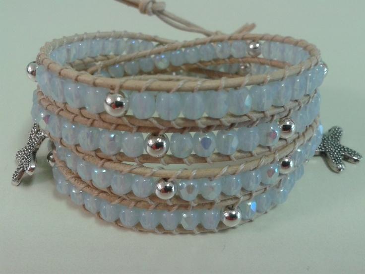 Quattro giri con mezzi cristalli color azzurro, perline color argento, cuoio neutro e stelline marine color argento.