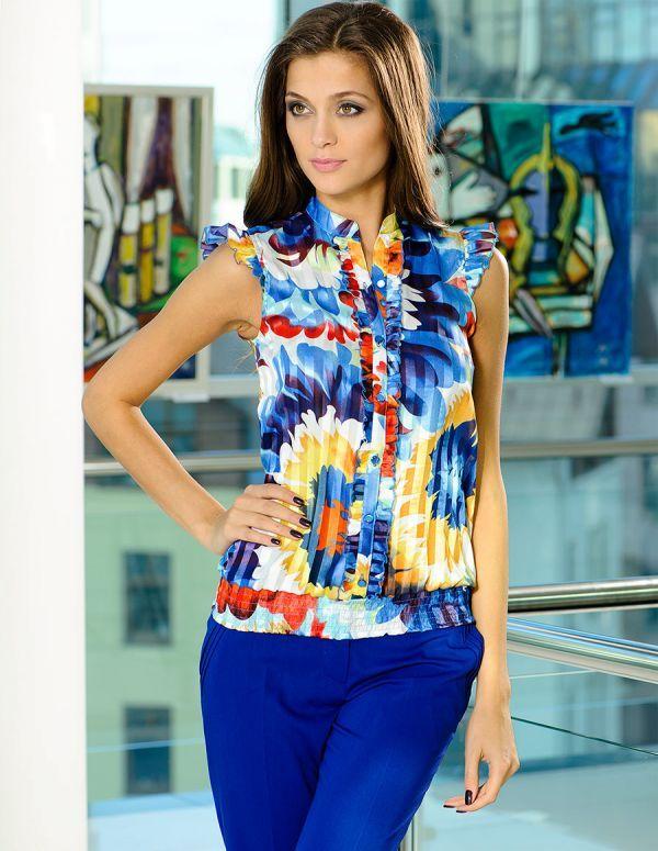 Очаровательная блузка без рукавов с ярким цветочным принтом. Имеет воротник-стойку и застёжку на пуговицы. Идеально подойдёт к однотонным вещам.
