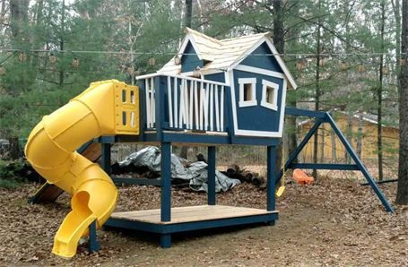 Dark Blue Elevated Playhouse with Tube Slide : Single dormer playhouse elevated to a 5' deck height with a lower deck, swing beam, and tube slide.