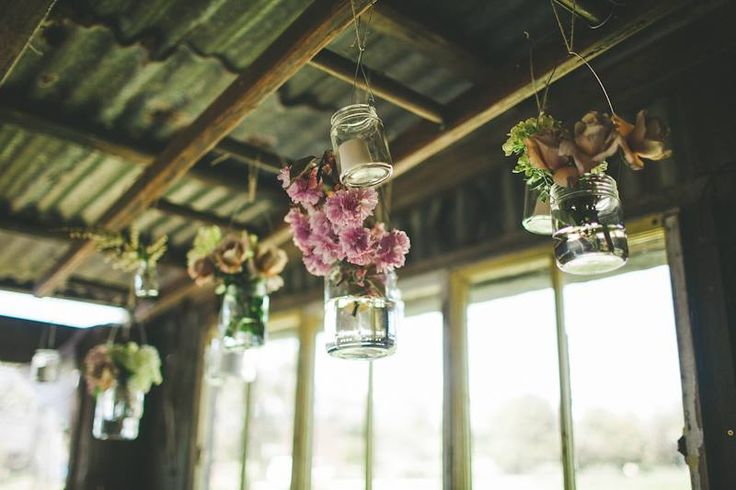 Glass jars hanging from the roof with wild flowers #ivyandmoss #wildflowers #boho #eventstyling #wedding #country #vintage