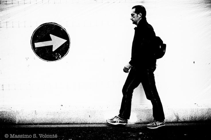 Man walking along a fence and against an arrow sign