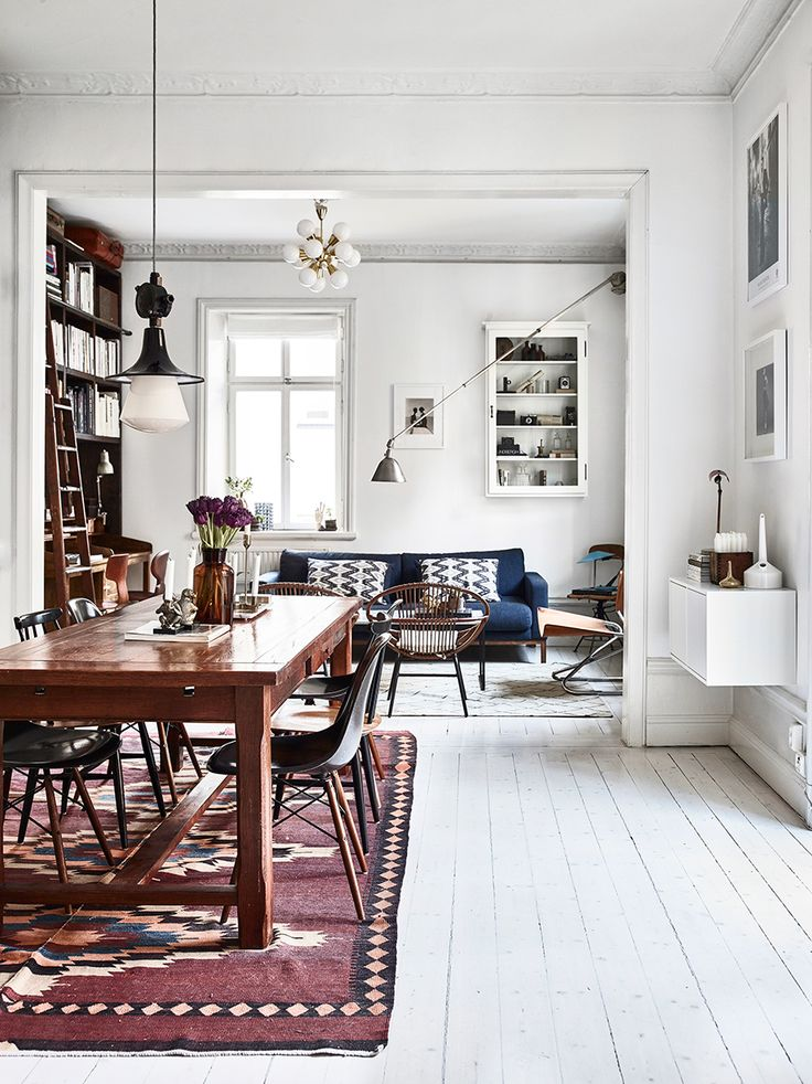 Photographer Kalle Gustafsson apartment styled by Dusty Deco with vintage interior. Bookshelves, fireplace, living room, dining room, white floors, wooden table, eames chairs..