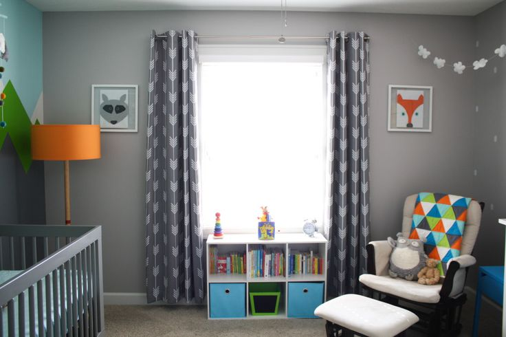 Unexpected art, modern triangle quilt, arrow curtains, and mountain mural over the crib.