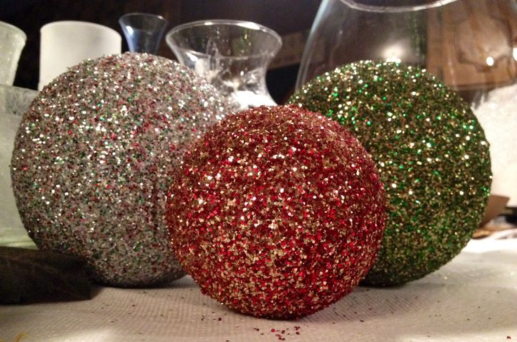 DIY Christmas balls!!! So cheap and quick to make. Only 3 items needed: styrofoam balls (any size), mod podge (Walmart craft section), and glitter. Use a foam brush to apply mod podge to the styrofoam (I used a fork to hold to hold the ball without smearing the glue). Roll or sprinkle with glitter. You can use only one color of glitter or mix different colors in a bowl like I did ^^^ Hang with tulle or arrange in a vase during the Christmas Holliday for eye-catching decor!